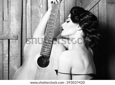 Sensual elegant retro glamour young adult woman with beautiful hair style red lips and bare shoulder holding acoustic string musical instrument of guitar indoor on wooden background, horizontal photo