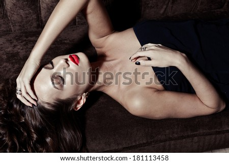 sensual elegant young woman in black dress on sofa indoor shot - stock photo