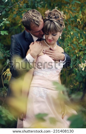 sensual embrace of the wedding couple on nature - stock photo