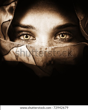 Sensual eyes of mysterious woman behind scarf - stock photo