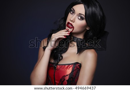 Sensual female vampire with blood on the lips