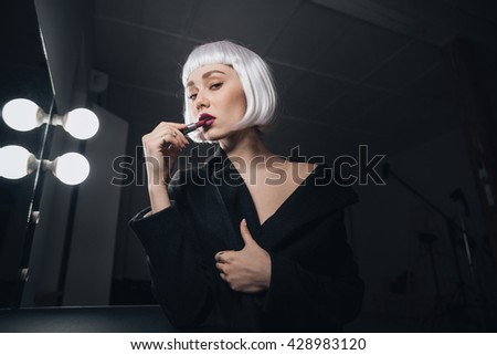 Sensual gentle young woman in blonde wig applying lipstick in dressing room