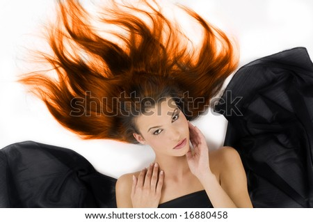 sensual girl laying down with hair in flame on floor and black fabric around