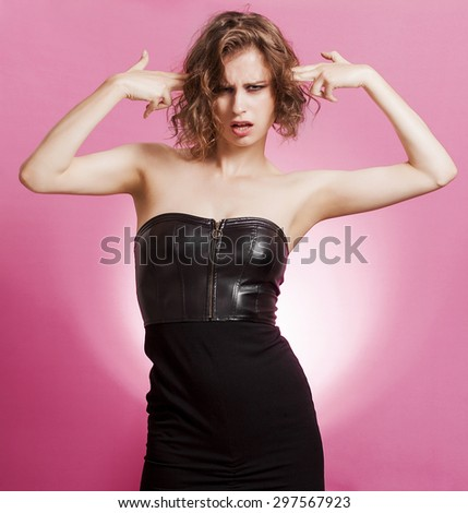 Sensual girl portrait making gun gestures and shooting herself
