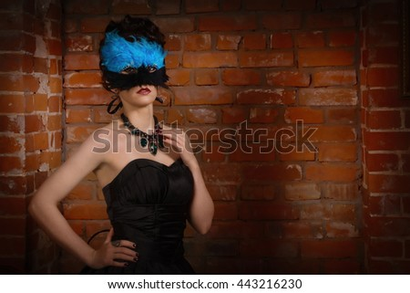 Sensual gothic woman in a long gorgeous black dress and mask at dark interior