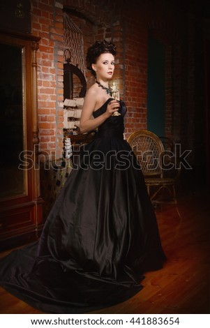 Sensual gothic woman in a long gorgeous black dress at dark interior - stock photo