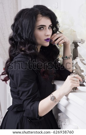 Sensual gothic woman in a long gorgeous black dress at white interior