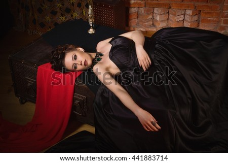 Sensual gothic woman in a long gorgeous black dress lying in a dark interior - stock photo