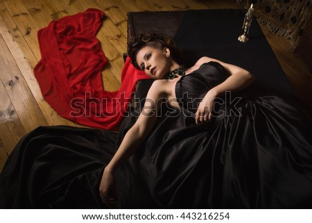 Sensual gothic woman in a long gorgeous black dress lying in a dark interior