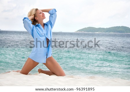 Sensual happy blonde woman on the beach in men's shirt