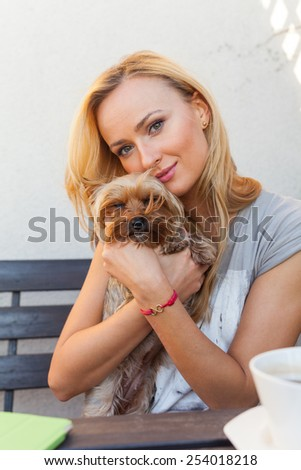 Sensual happy blonde woman sitting on wooden bench with her dog. - stock photo
