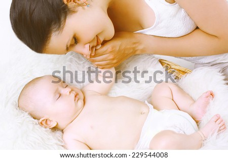 Sensual happy mother and sleep baby in bed home - stock photo