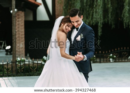 Sensual happy newlywed couple dancing outdoors at reception - stock photo