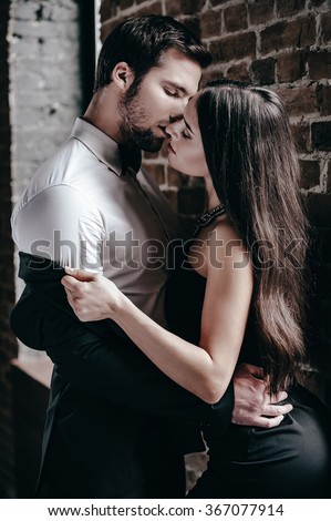 Sensual kiss. Beautiful young woman in cocktail dress leaning to her boyfriend and taking off his jacket while standing near brick wall in loft interior - stock photo