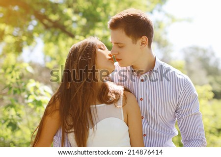 Sensual kiss young couple in summer day - stock photo