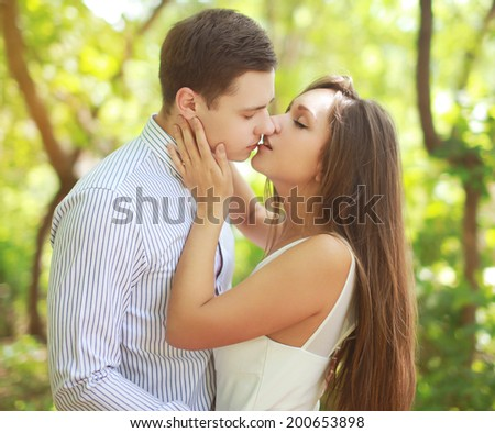 Sensual kiss young couple outdoors - stock photo