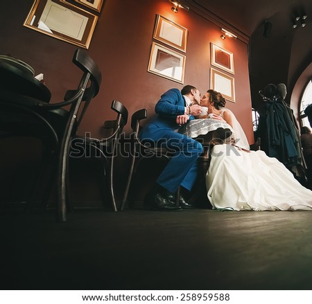 sensual kissing couple sitting with cups of coffee