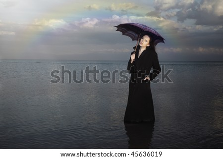 Sensual lady in the black coat with umbrella standing in the water after the rain. Rainbow on a background