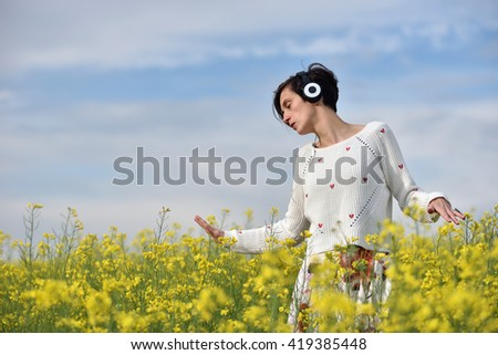 Sensual lady listening music in headphones and dancing in a canola field - stock photo