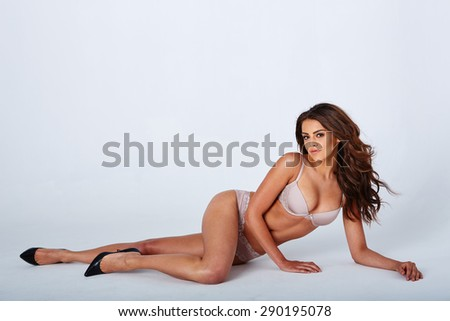 Sensual lady posing in  sexy lingerie while isolated - stock photo