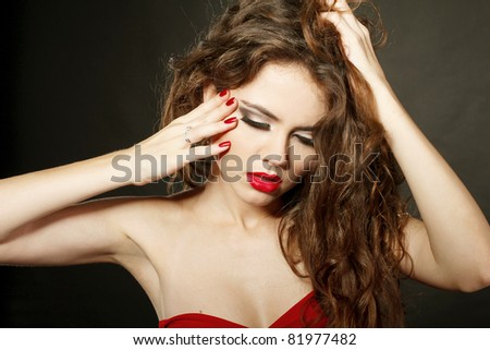 Sensual lady with red lips and red nails, touching face - stock photo