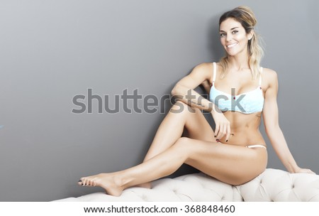 Sensual latin blond woman in lingerie lying on a sofa - stock photo