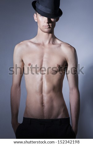 Sensual man with beautiful face, muscular torso and hands in his pockets, dressed in black hat and trousers. - stock photo