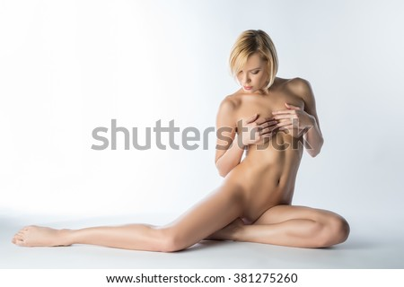 Sensual naked blonde posing covering her breasts - stock photo