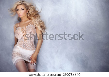 Sensual naked blonde woman posing in white sexy lingerie, looking at camera. Long hairstyle. Perfect body. - stock photo