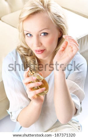 Sensual perfume - woman test perfume on her wrist .Form of a beautiful blonde holding in his hand a bottle of perfume  - stock photo