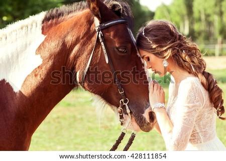 Sensual photo of young beautiful bride hugging a horse - stock photo
