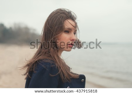 sensual portrait of a beautiful stylish girl on the beach on a windy day