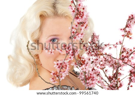 Sensual portrait of a spring woman with flowers on the face and  fancy makeup  cherry blossom portrait studio shoot isolated  on the white.