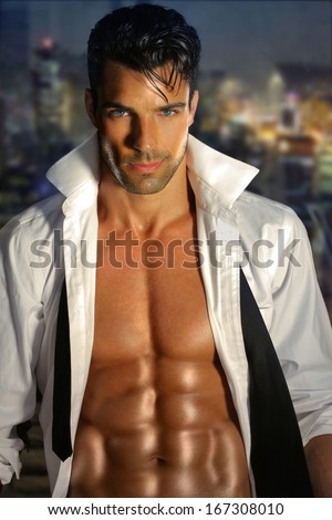 Sensual portrait of a very handsome muscular man with open shirt and hot body against window at night