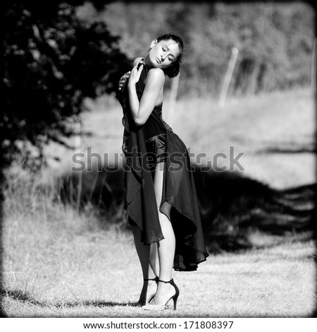 Sensual portrait of a woman dancing outdoors.