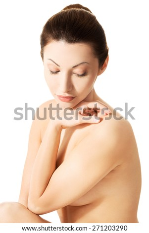 Sensual portrait of nude caucasian female sitting.