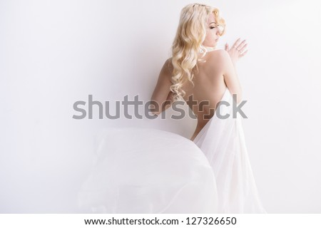Sensual portrait of young attractive blond with transparent cloth over wall. Lot of copy space - stock photo