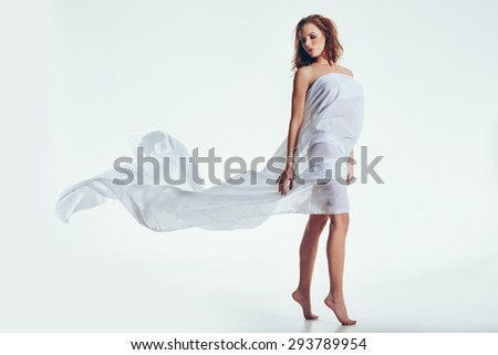 Sensual portrait of young attractive brunette with transparent cloth. Naked woman posing over white background - stock photo