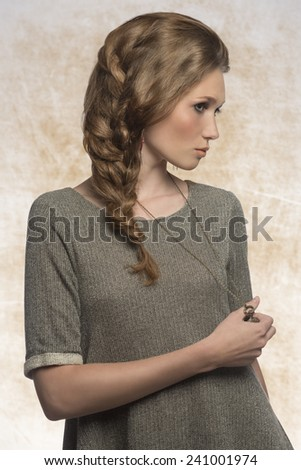 sensual pretty woman with long plait and gray dress, wearing stylish necklace and earrings. In fashion pose  - stock photo