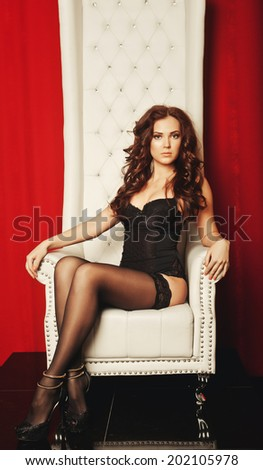 sensual princess woman in black lingerie sitting on throne
