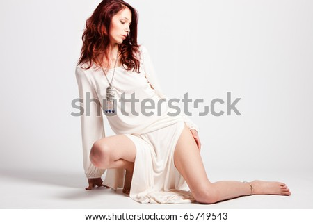 sensual red hair fashion woman in elegant fine white dress, studio shot