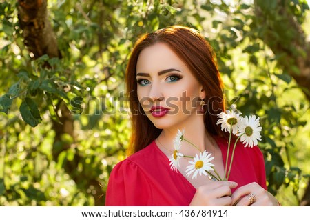 Sensual red haired young woman with fresh skin and beauty makeup holding bright bouquet of daisies outdoors - stock photo