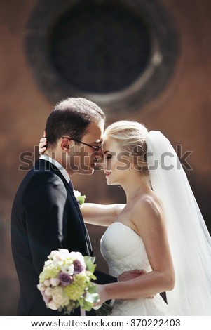 Sensual romantic couple of newlyweds hugging in front of old church closeup