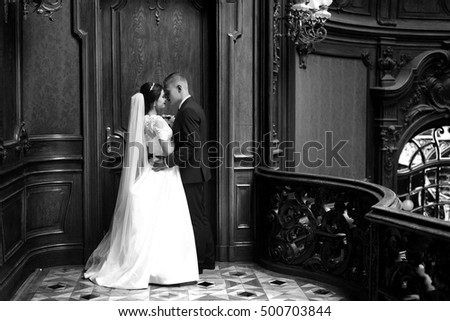Sensual romantic newlywed couple, bride and groom kissing on baroque wooden balcony