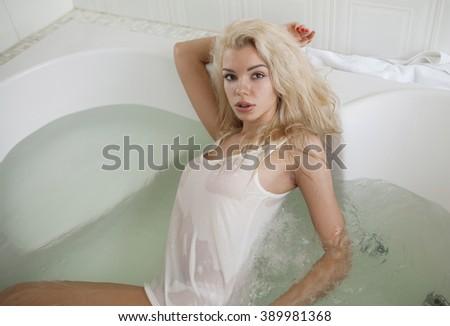 Sensual sexy blonde girl relaxing in bath foam - stock photo