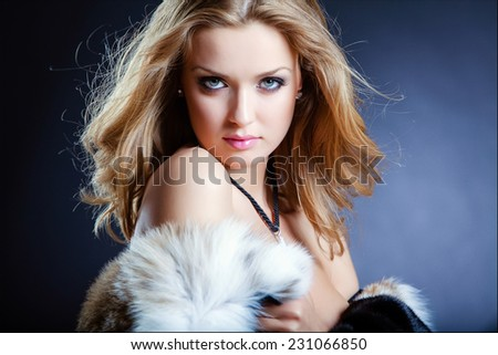 Sensual sexy girl blonde in a fur coat on a blue background, close up - stock photo