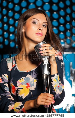 Sensual singer with retro mike, close up shot - stock photo