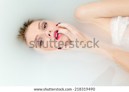 sensual spa: closeup on mouth open in pleasure blond elegant pinup girl having fun happy relaxing laying in clear water on copy space background portrait - stock photo