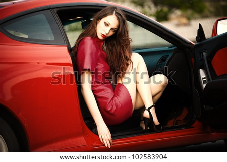 sensual stylish woman sit in red car - stock photo