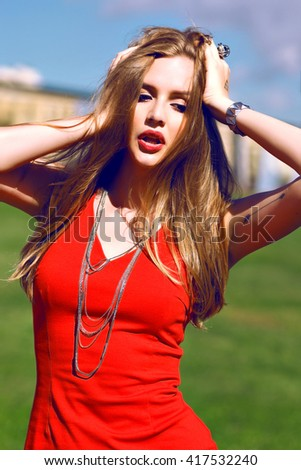 Sensual summer portrait of pretty woman, long stunning blonde hairs, natural make up, windy weather, sexy mini red dress, green grass, beautiful sunny day. close her eyes and enjoy. - stock photo